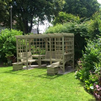 The Riviera Seated Pergola, wooden garden corner arbour seat with table and trellis